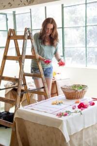 עומדת על סולם ומעצבת סט צילומים של פרחים