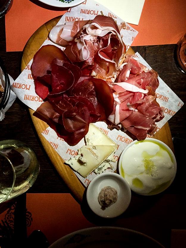 OsteriaMorini מגש נדיב של אנטיפסטי נקניקים, לחם, גבינות ושמן זית, ואנחנו מתנדנדים בהנאה לקצב הפסקול האיטלקי.