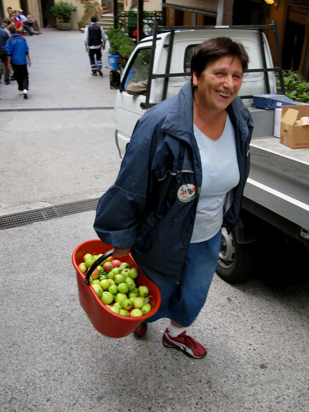 במעלה הרחוב הראשי של מנרולה, אישה נושאת סל תפוחים טריים, שזה רק נקטפו.