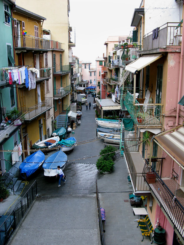 ברחוב ראשי של מנרולה, חונות סירות דייגים לצידי הבתים, המסעדות והטרטוריות,