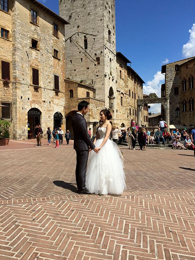 כמה רומנטי, חתן וכלה מצטלמים בכיכר העיירה San Gimignano שהיא ללא ספק מהעיירות היפות ביותר בטוסקנה