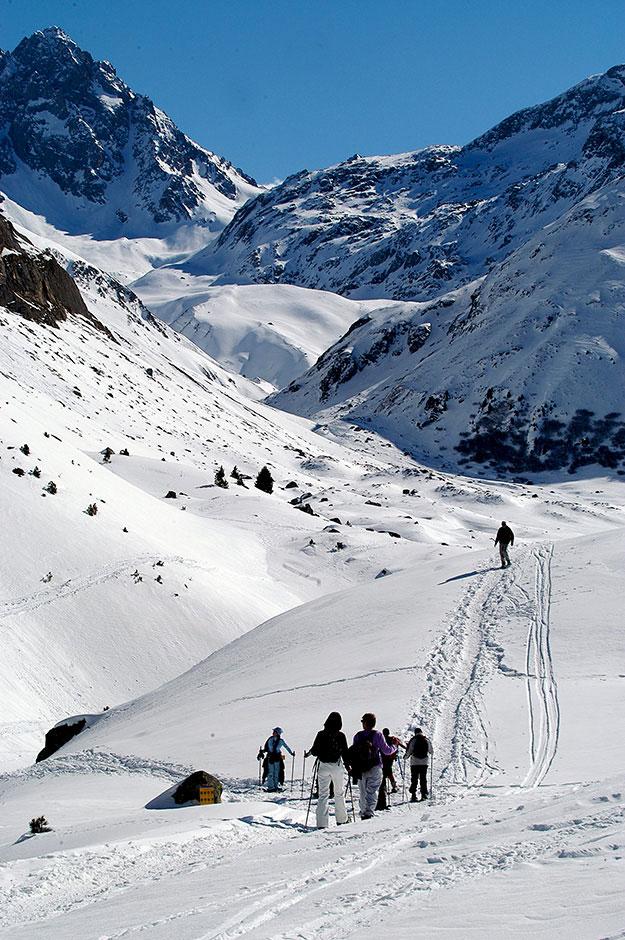 הנוף הלבן נפרש ומהפנט, מהרכבל אפשר להבחין בגולשים החרוצים יורדים במדרונות. עושיםסנואו שואינג, הליכה מאומצת בשלג בנוף לבן מהפנט או ביער אורנים
