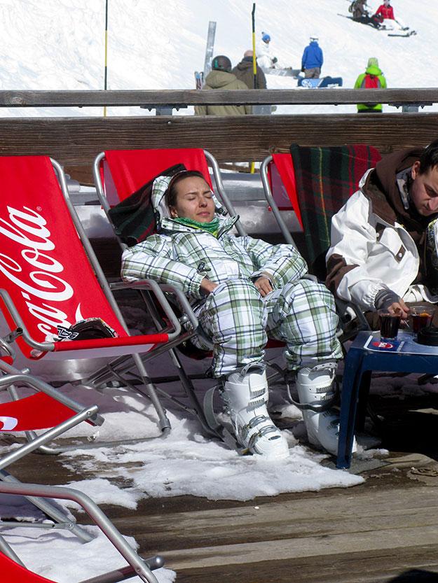 גולשת בלבוש סקי אופנתי תופסת מנוחה בשמש