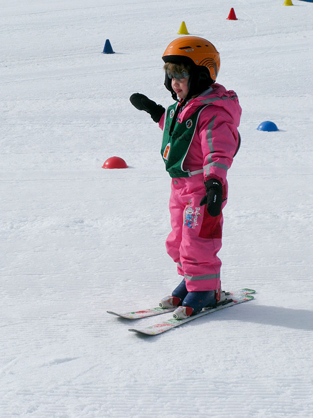 ילדה בחליפת סקי ורודה בשיעור גלישה