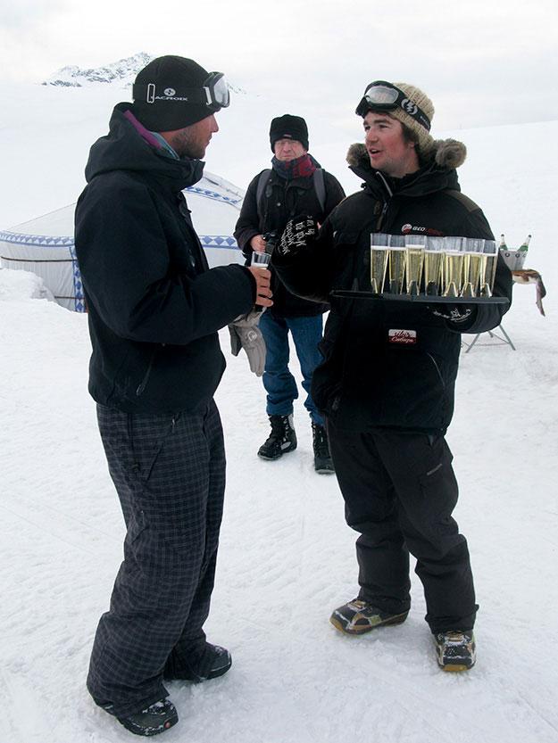 גביע של שמפניה שצוננה במקרר טבעי חצוב בתוך הקרח ומתאבנים קטנים מקבלי את פני האורחים