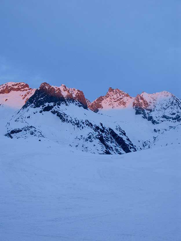 שקיעה כתומה על פסגות ההרים המושלגים