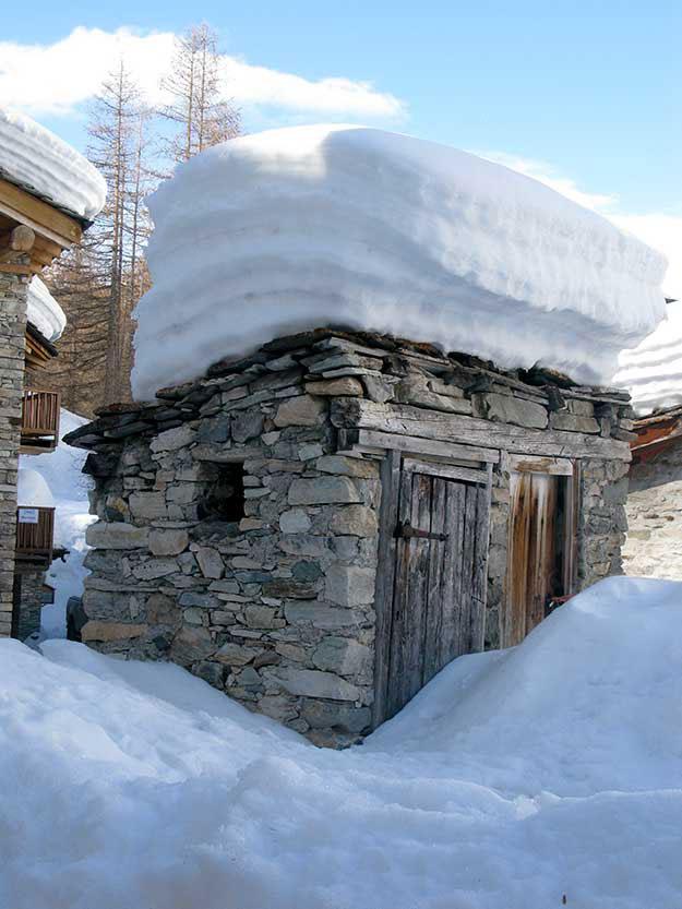 בתי אבן נמוכים מכוסים בשלג שנערם כמו מצנפות שינה כבדות על גגות הרעפים