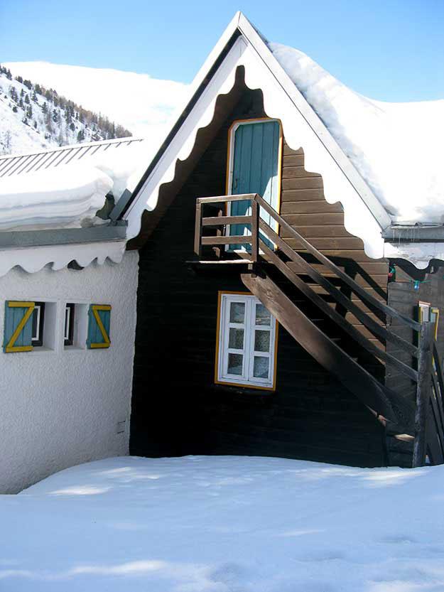 בית אבן עם שתי דלתות כניסה, אחת ממוקמת מעל השנייה וגרם מדרגות עץ צר מוביל את הדלת העליונה. מתברר, שדלת אחת משמשת כדלת כניסה בקיץ, זו הדלת התחתונה. בחורף כשהשלג נערם לגובה כזה שמכסה את הגישה לבית, נעזרים בדלת העליונה כדלת הכניסה בחורף