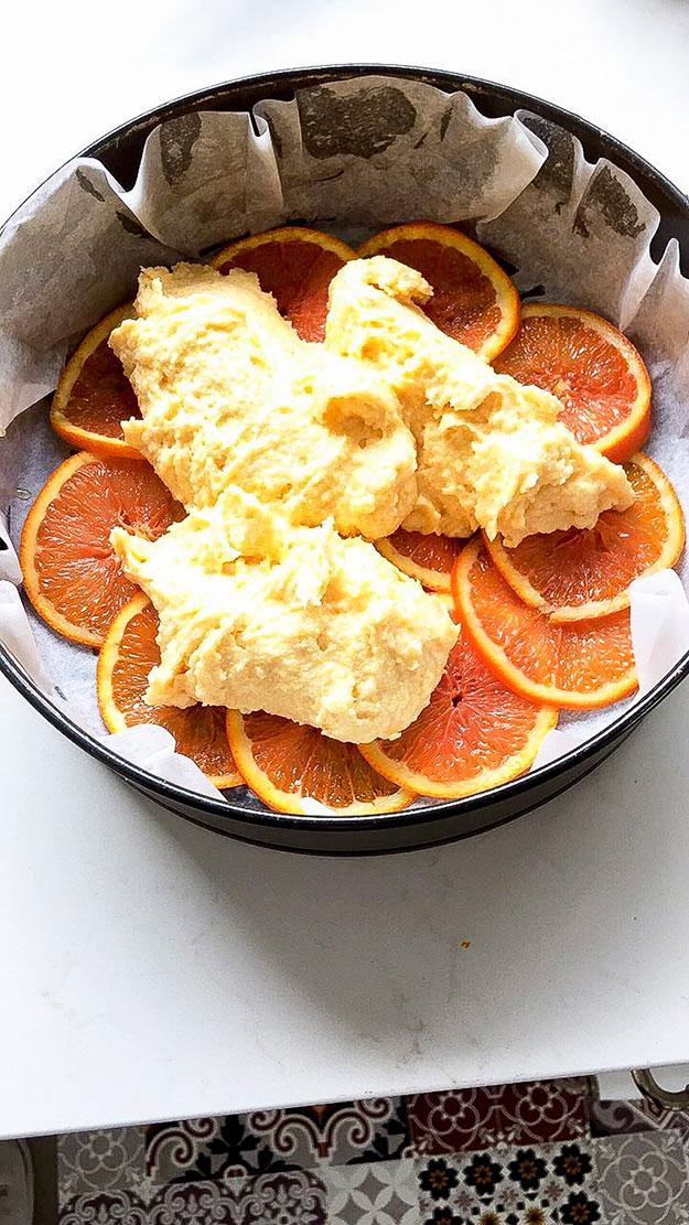 יוצקים לתבנית האפייה מעל התפוזים את התערובת ומחליקים את פני השטח הבלילה