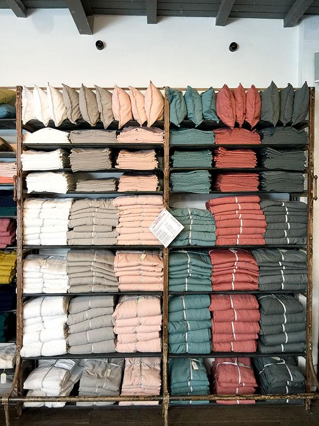 מדפים עמוסים במצעים וטקסטיל לבית של MERCI