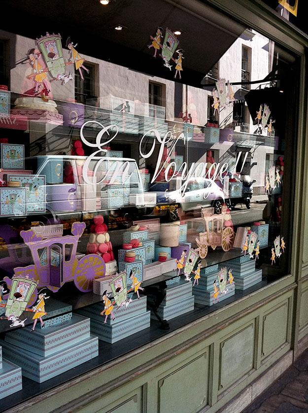 החזית הירוקה עם חלון ראווה עמוס במגדלי קופסאות בצבעי פסטל ומיצג מקרונים של Laduree