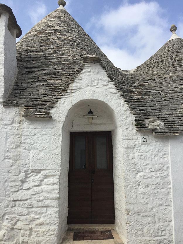 בתי טרולי ממבנים קטנים עגולים, מסוידים בלבן, בעלי גגות עץ בצורת חרוט