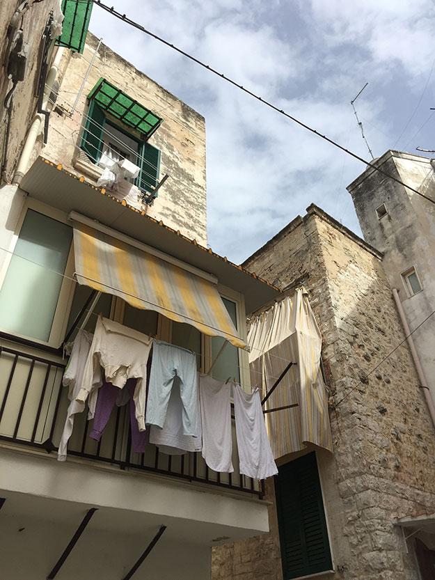 בסמטאות בארי בתים בצבעי חמים וכביסה תלויה
