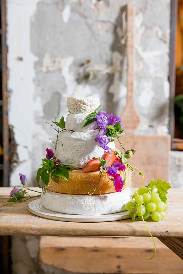 מגדל גבינות קטן מגבינות עיזים, בקר וצאן, מעוטר בתותים, פרחים וענבים