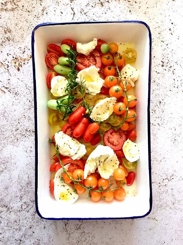 תבנית של עגבניות, מוצרלה ושמן זית מוכנה לצלייה בתנור