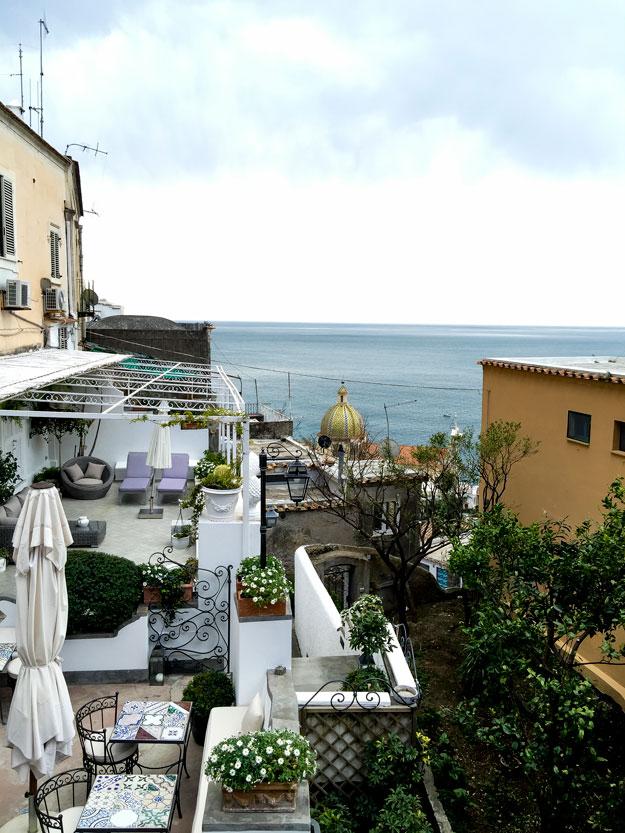 מהמרפסת אפשר לראות את כיפת הכנסייה המוזהבת, הנוצצת של פוזיטנו והים הכחול.