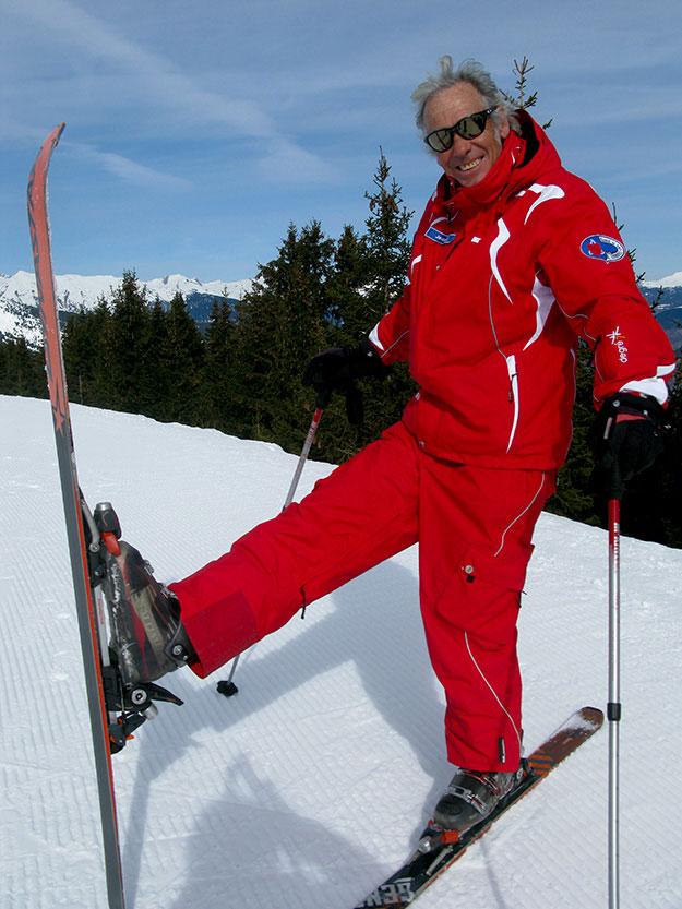 מדריך סקי לבוש חליפת סקי אדומה מדגים עמידה על סקי אחד