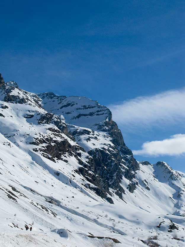 שמים כחולים ועננים לבנים בפסגת ההר