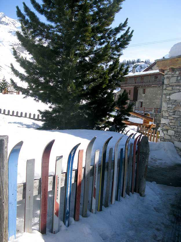 מגלשי עץ ישנים, צבעוניים בגדלים שונים, משמשים כגדר