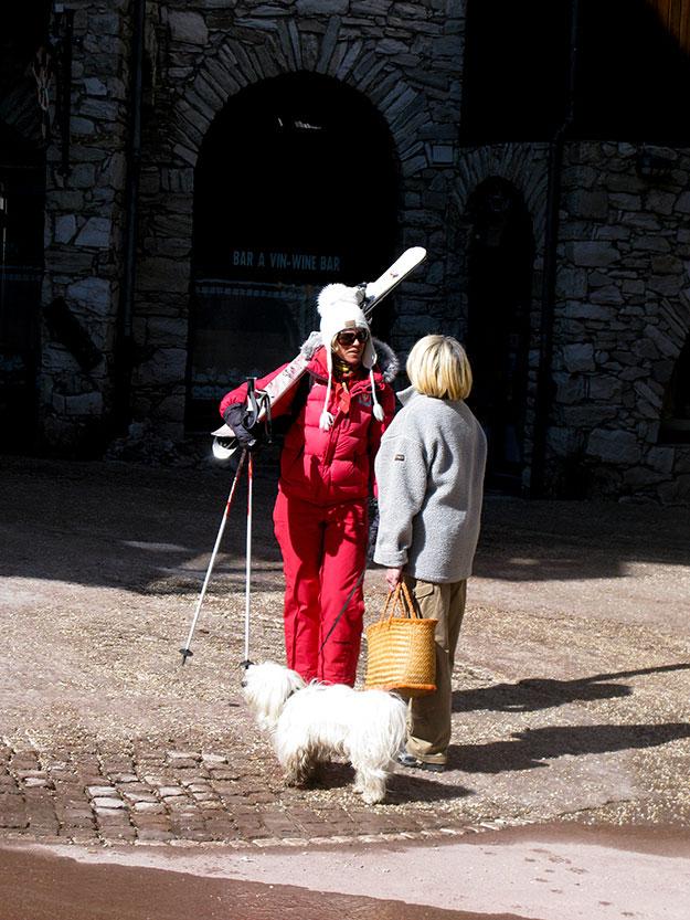 אשה עם כלב ואשה לבושה בחליפת סקי אדומה משוחחות זו עם זו