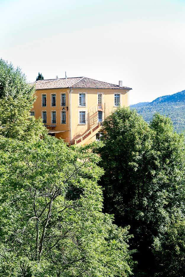 הבתים פזורים על ראש של צוק סלעי על רקע שמים כחולים של פרובאנס ונראים מצוירים כמו גלויה על רקע הנוף