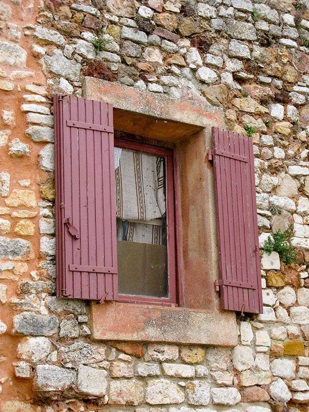 חלון עץ בגוון טרקוטה בעיירה האדומה רוסיו
