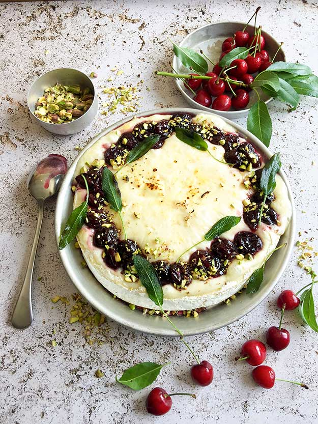 גבינת קממברט יעקבס אפויה בתנור מוגשת כמו טארט עם דובדבנים ופיסטוקים