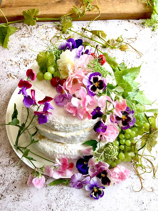מגדל גבינות של משק גבינות יעקובס מעוטר בפירות ופרחים בצורת עוגת קומות שיצרתי לכבוד יריד הביכורים לחג שבועות של משק גבינות יעקבס בכפר הרוא״ה.