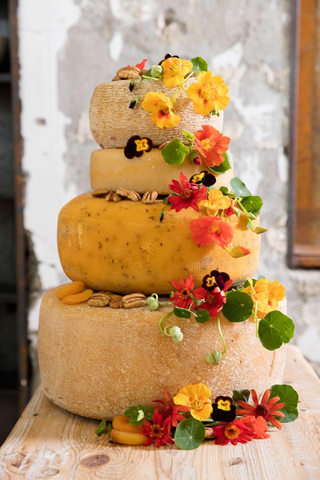 מגדל גבינות צהובות, בצורת עוגת קומות, מעוטר בפירות יבשים, פרחים ואגוזים